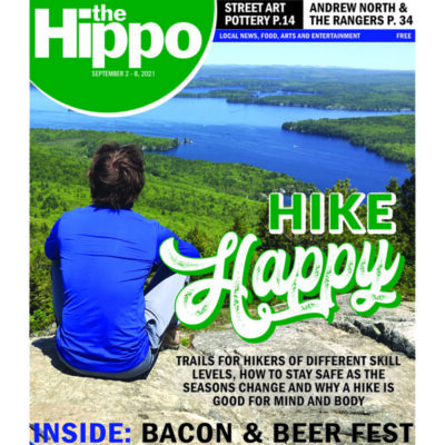 cover of newspaper, man shown from back, sitting on rocky peak overlooking forest and lake