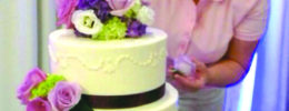 woman adding flower decorations to 3 tiered white frosted cake
