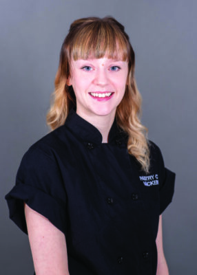 portrait of woman smiling, wearing black chef's shirt
