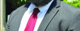 portrait of young man with afro and beard, wearing suit and glasses, standing outside