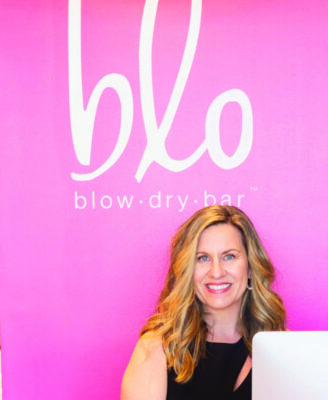 woman sitting in front of pink wall on which her business name is painted