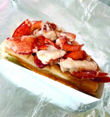 lobster roll in cardboard takeaway container, sitting on silver wrapper