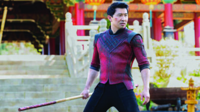 movie still, depicting asian man in red shirt, holding wooden staff and standing in fighting stance