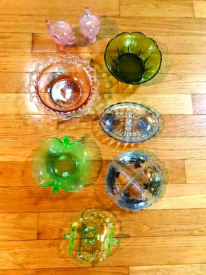 assorted old glassware seen from above on wood floor