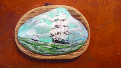 miniature painting of ship, painted on sea shell, sitting on wood