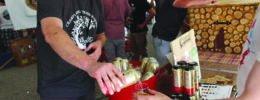 man behind event table pouring beer sample