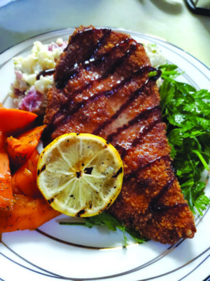 breaded chicken on greens, with carrots and a slice of lemon, on plate
